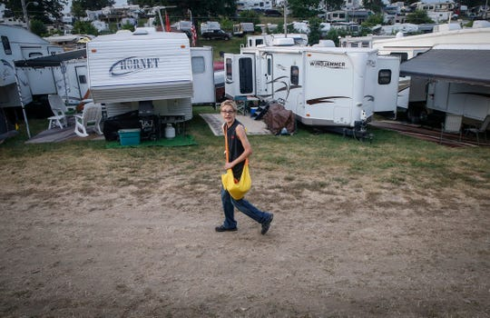 Dredun Gunn, 16, of Des Moines, walks around the Iowa State Fair campground on Tuesday, Aug. 14, 2018, in Des Moines, selling individual copies of the Des Moines Register to campers.