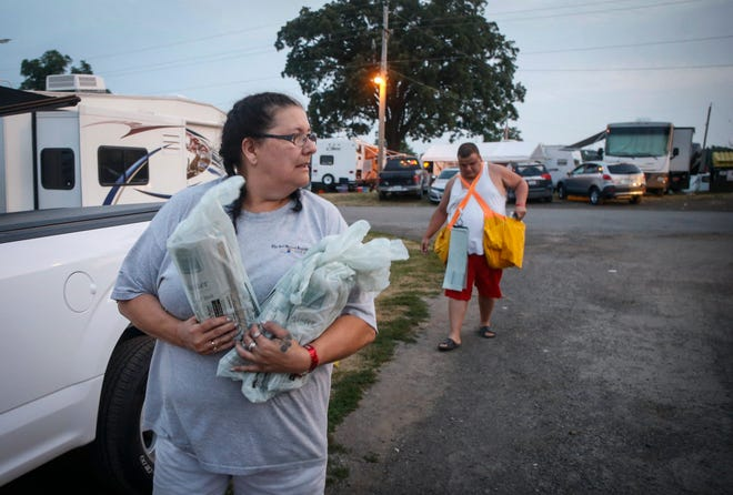 Lisa Sharp and her son, Dallas Sharp, deliver copies of the Des Moines Register throughout the Iowa State Fair campgrounds on Tuesday, Aug. 14, 2018, in Des Moines.