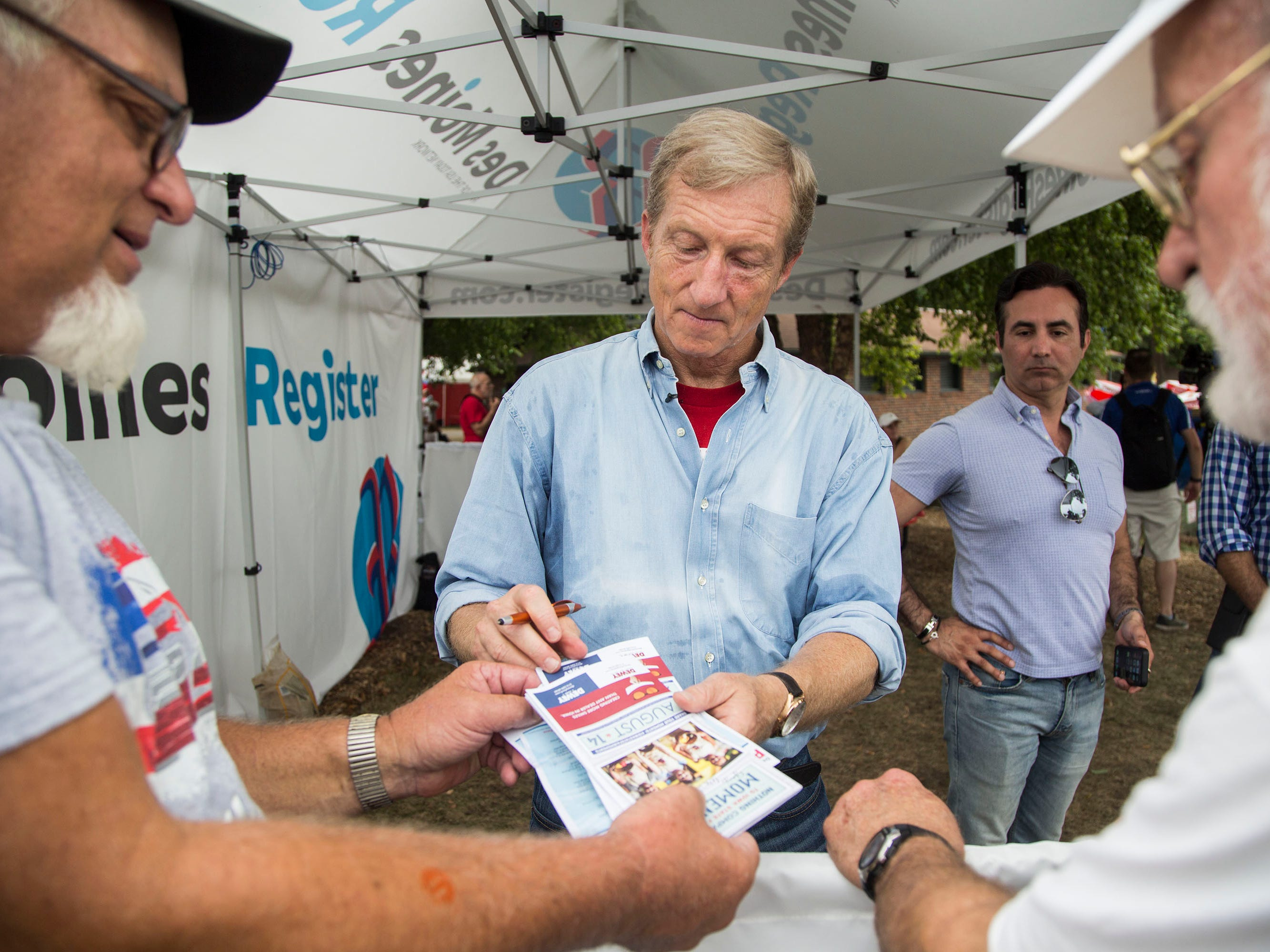 Tom Steyer, a Democratic donor and activist from California, signs autographs after speaking at the Des Moines Register Political Soapbox on Tuesday, Aug. 14, 2018, at the Iowa State Fair.