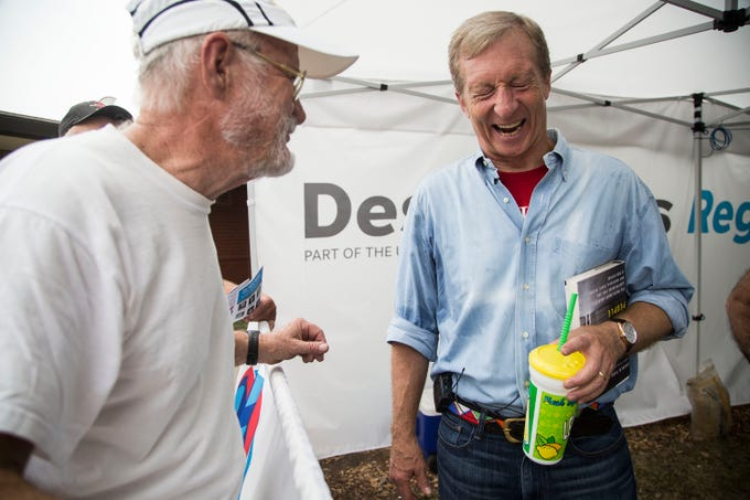 Tom Steyer, a billionaire hedge fund manager known for his environmental philanthropy and Democratic campaign support, laughs while talking with a fairgoer after speaking at the Des Moines Register Political Soapbox on Tuesday, Aug. 14, 2018, at the Iowa State Fair.
