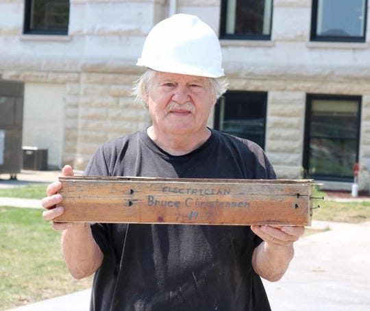 Bruce Christensen shows the wood on which he etched his name exactly 41 years, to the day, before the July 19 tornado that damaged much of Marshalltown, Iowa.