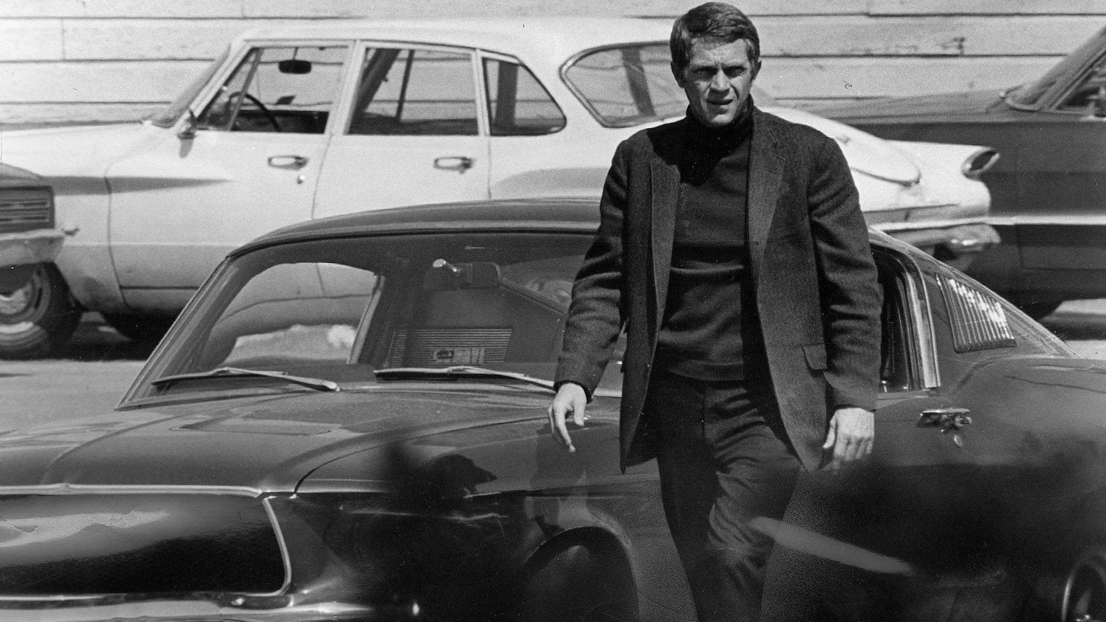 """Steve McQueen, starring in the title role of """"Bullitt,"""" steps out of his car after a 140-mile-an-hour pursuit through the hilly streets of San Francisco.  The Technicolor action drama was filmed entirely on location in the Bay City."""