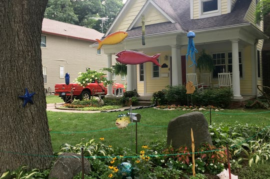 Larry and Sandra Wilson live at the house on Mortenson Boulevard in Berkley, where passersby can see a giant chair, a marionette, shark fins, dancing stick figures and more homemade wooden items.