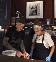 Executive Chef Aaron Solley, left, shows Raw Bar cook Neishma Balaguer how to properly open an oyster.
