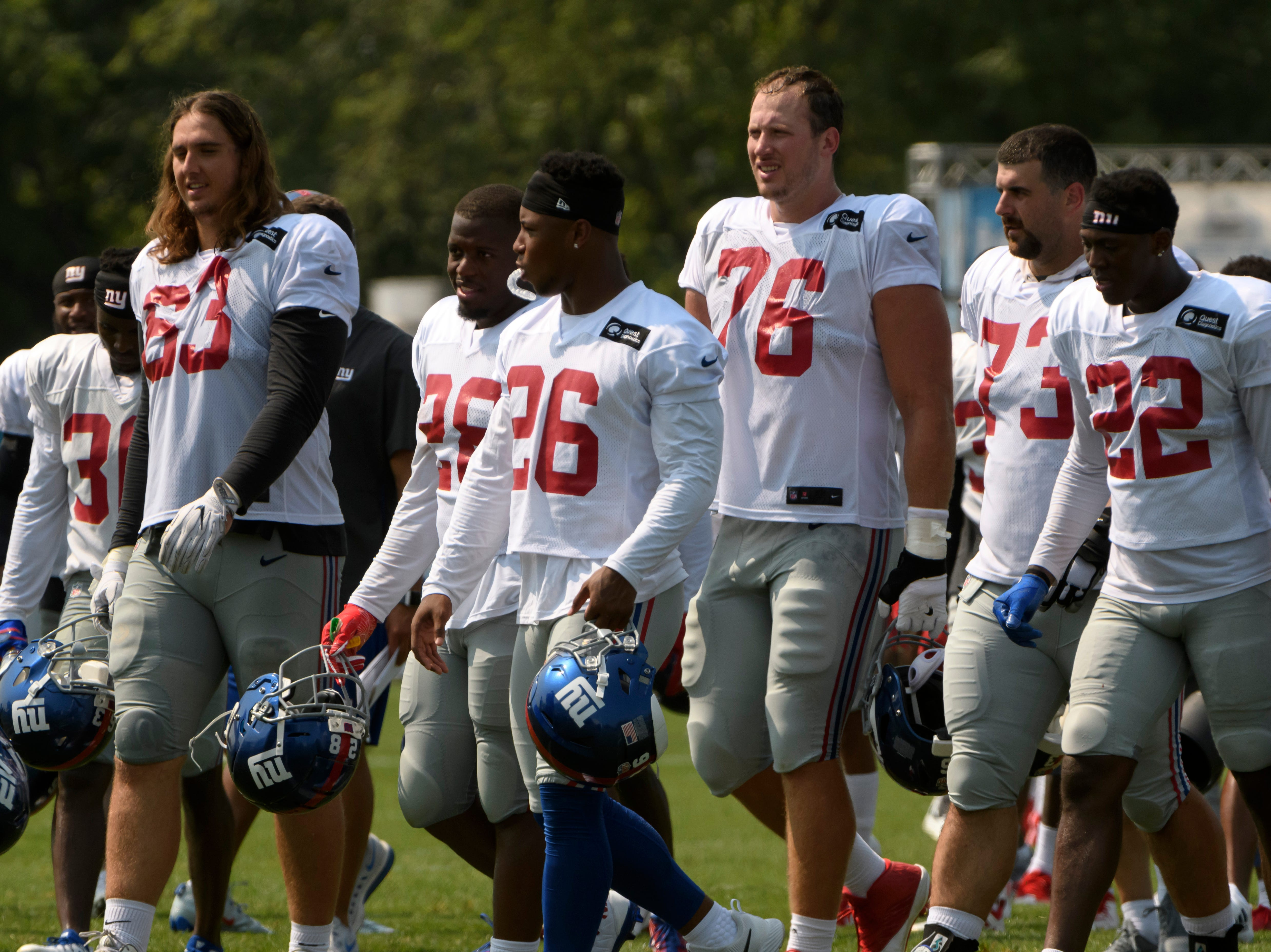 The New York Giants walk off the field after practice.