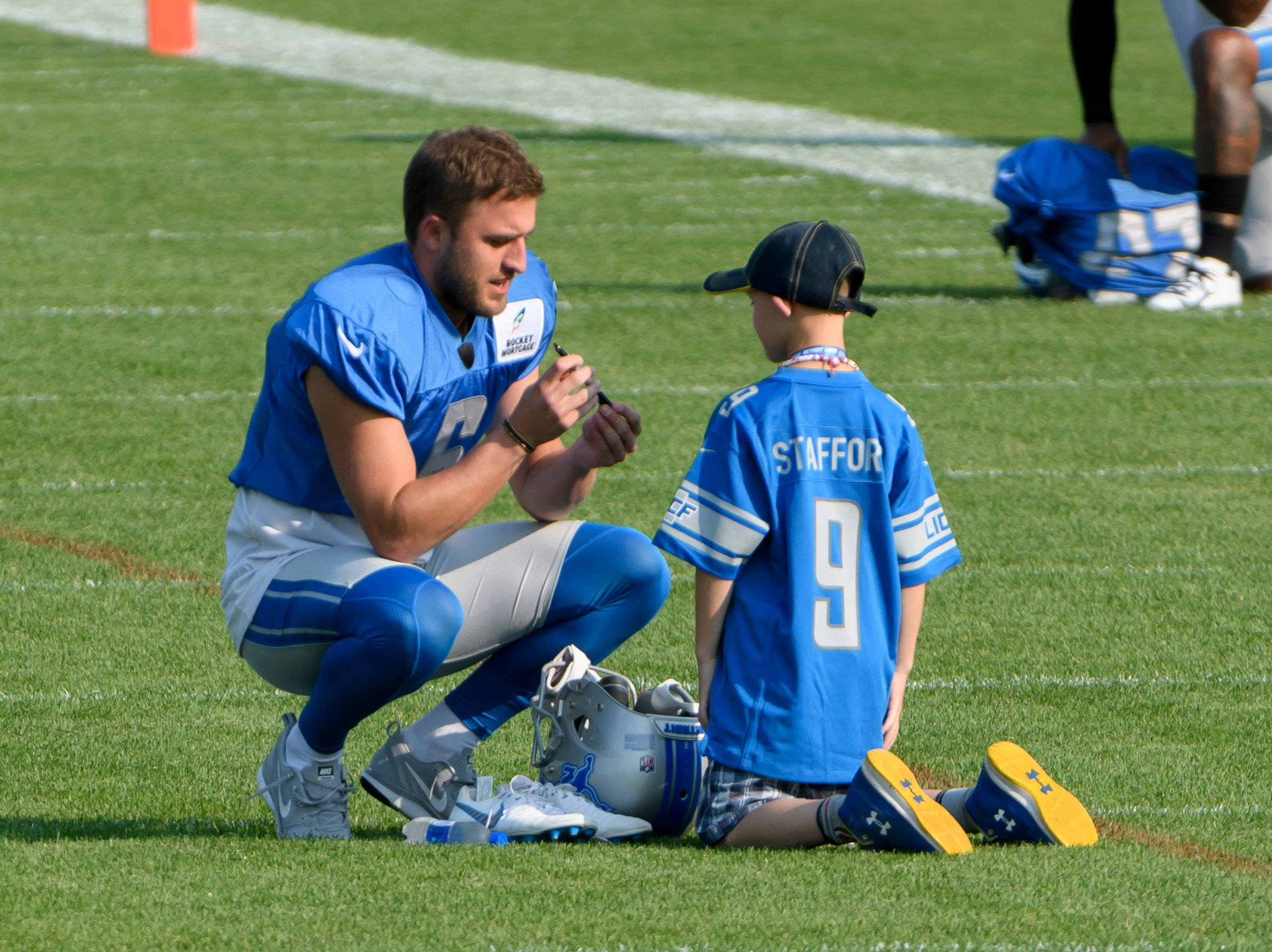 Lions punter Sam Martin signs an autograph for a fan before the start of practice.