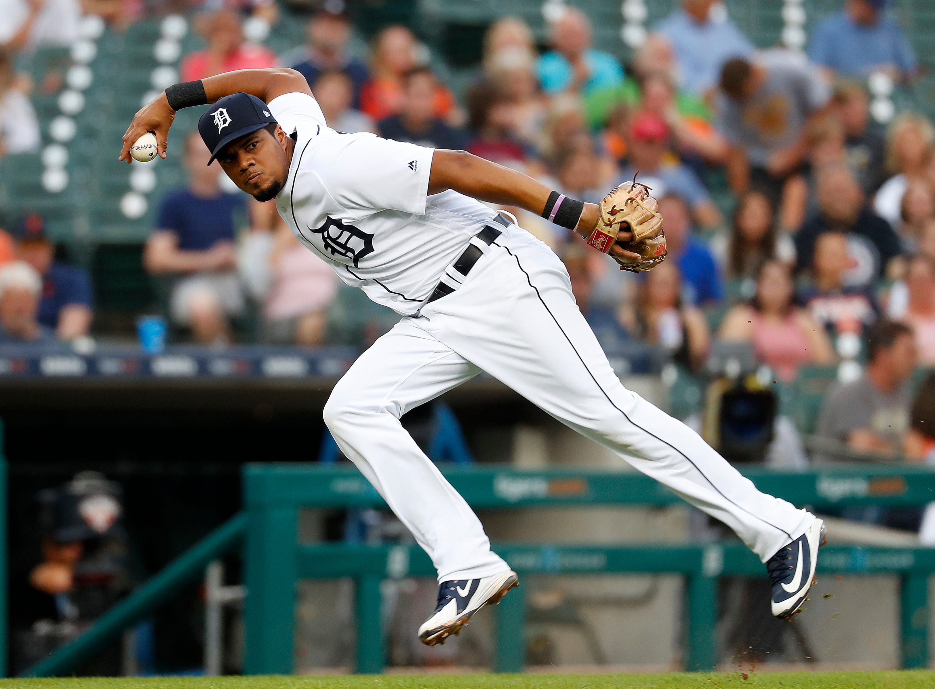 Detroit Tigers third baseman Jeimer Candelario throws to first base on Chicago White Sox's Yolmer Sanchez bunt single in the third inning.