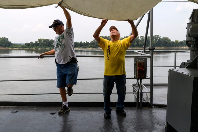 Scott Anderson of Evansville, left, and Dave Cassell of Cincinnati, Ohio, right, work with other volunteers to hang a canopy over a deck on the USS LST-325 in Evansville, Ind., Tuesday, Aug. 14, 2018. About 50 volunteer workers from all over the country will board the ship on Thursday for a month long sailing trip to Dubuque and Bettendorf, Iowa, and Chester, Ill., to educate the public about LST ships.