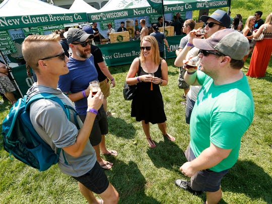 Jason Cassidy and Peter Granger, both of Madison, Emily Parmenter of Denver and Marty Schroeder and Sam Shannon, both of Madison, were among 6,000 people on hand to sample beers from 200 breweries from around the Midwest Saturday, August 11, 2018, in Olin Park in Madison.