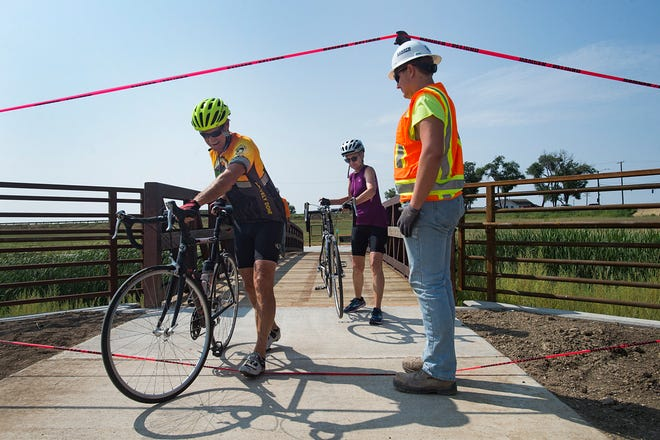 Barthmew Mansfield holds up some caution tape for Gary and Wendy Hurd as they check out the new sections of the Long View Trail on Loveland's north side on Tuesday, August 14, 2018. The trail runs north to south along Shield Street in Fort Collins and Taft Avenue in Loveland.