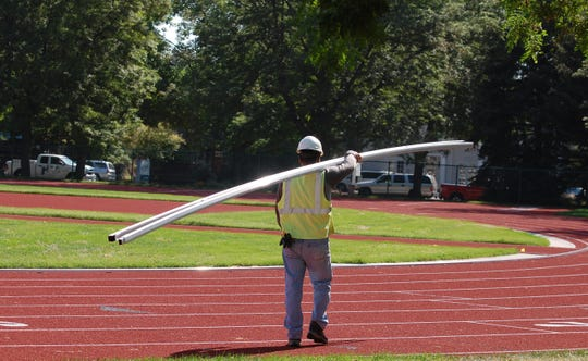 A worker carries metal curbing for the inside lane Aug. 8, 2018, as part of CSU's renovation of Jack Christiansen Memorial Track.