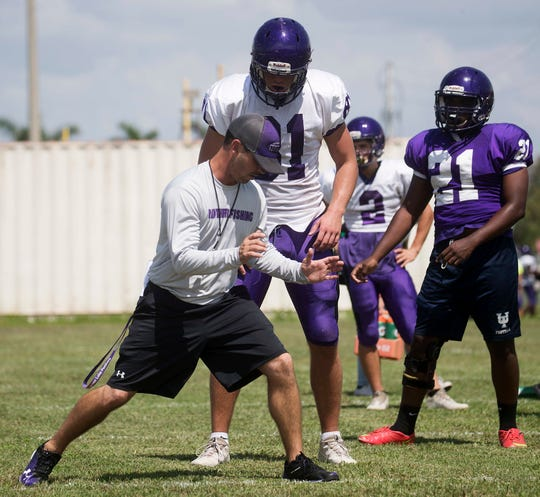 Richie Rode, the coach for the Cypress Lake High School football team works with Liam Ball during a practice on Monday 8/13/2018.