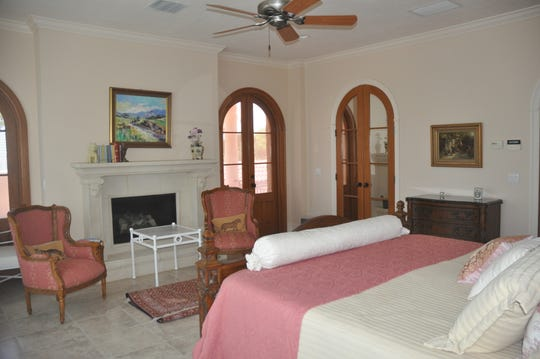 The master bedroom has a wall of windows overlooking the water and doors that lead to a terrace overlooking the courtyard and pool.