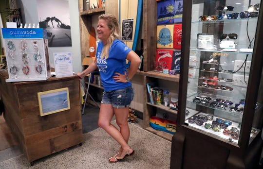 Jill Miller talks with customers renting bicycles on July 31 at EOS Surf & Outdoor Shop in downtown Sheboygan.