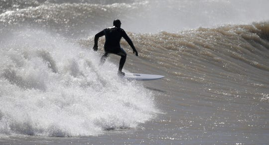 A surfer catches a wave April 4 near the south pier in Sheboygan.
