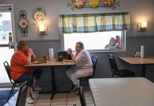 Suzanne McKeown, left, and Elaine Franklin eat lunch at Barn Xpress cafeteria while Lily Rawls and Mattie Gowings look in the restaurant window for their grandmother Ann Price, also eating lunch.