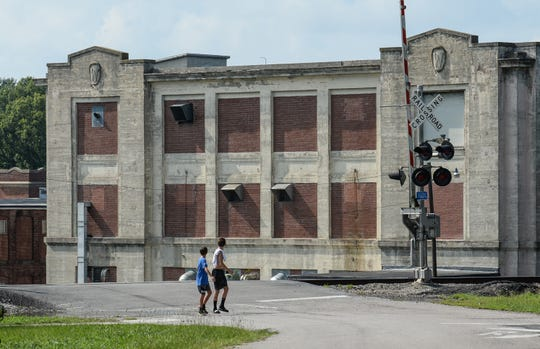 Two boys look back at the historic Winnsboro Mill, still open since 1897, but down to 30 employees.