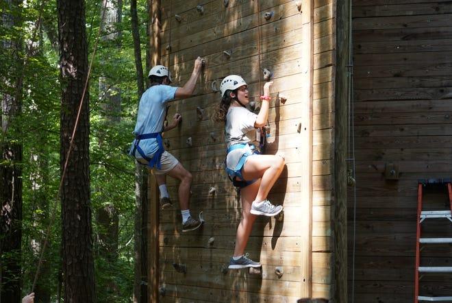 Children at Camp Kesem navigate a climbing wall.