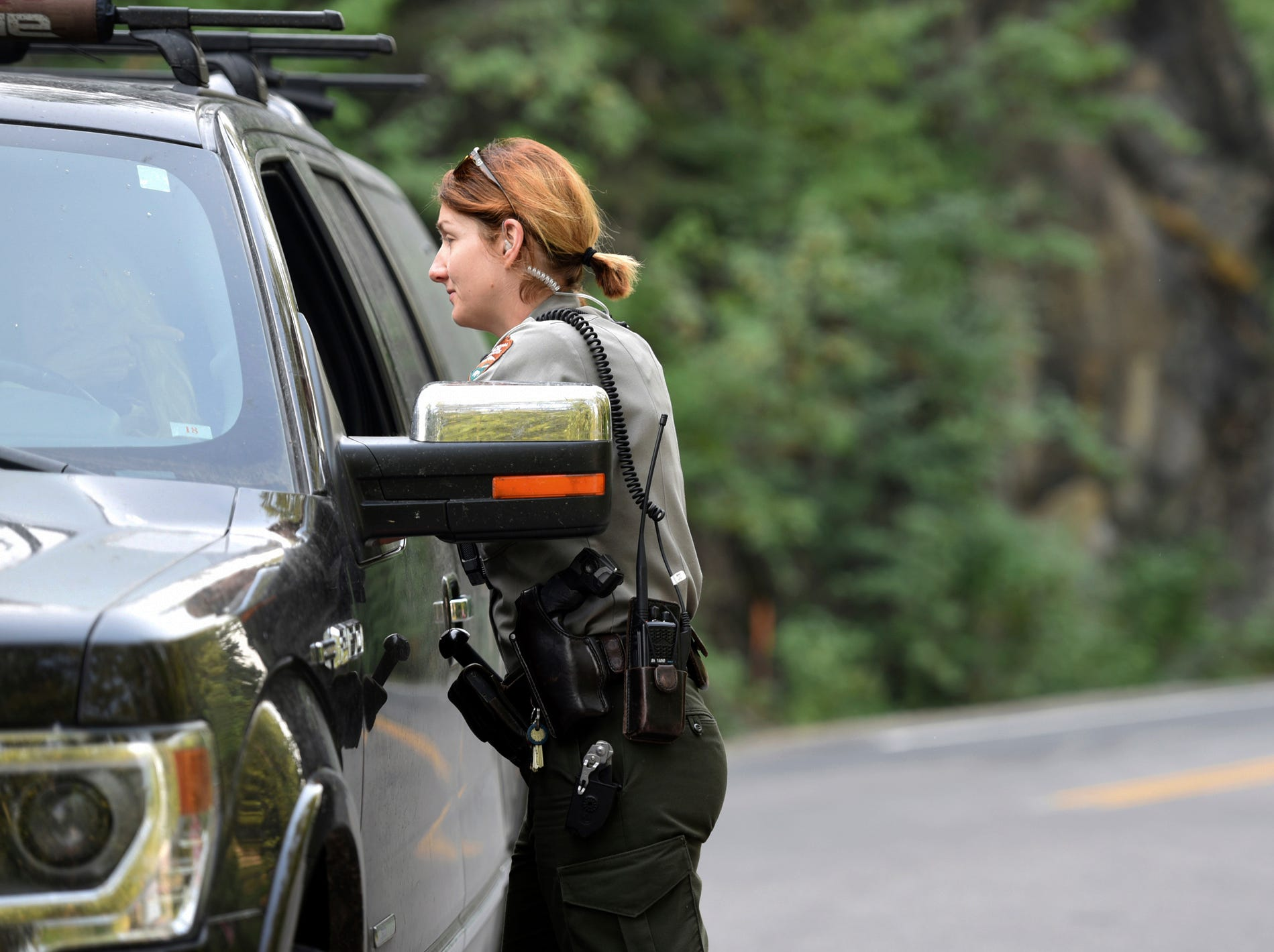 Park Ranger Elizabeth Boyden talks with a visitor at the intersection of Apgar Loop and Going-to-the-Sun Road in Glacier National Park on Monday, August 13. Visitors had to be stopped at Apgar and rerouted either to East Glacier, from which visitors can still reach Logan Pass, or toward North Glacier. (Brenda Ahearn/The Daily Inter Lake via AP)