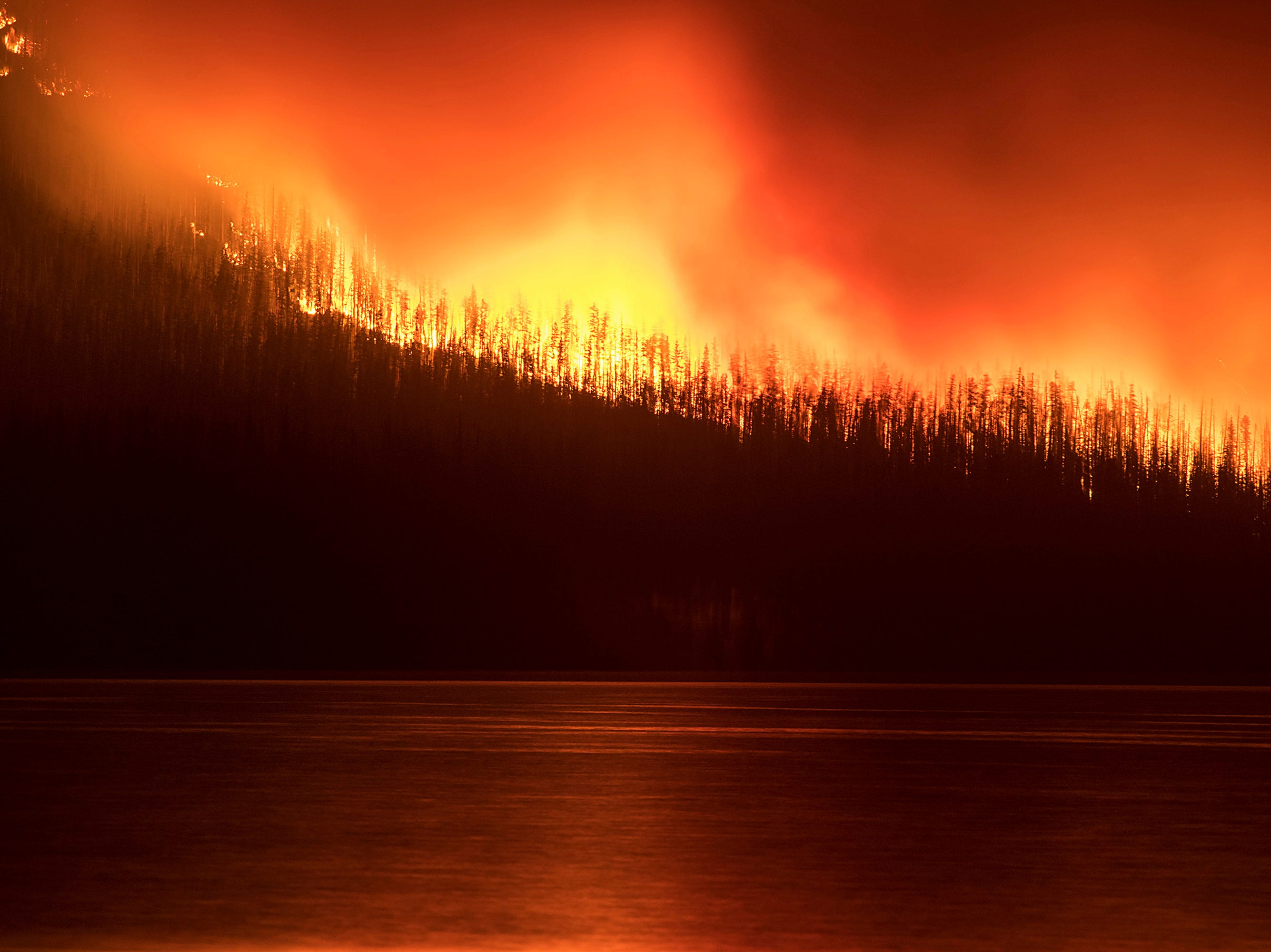 In this photo taken Sunday, Aug. 12, 2018, a fire burns next to Lake McDonald in Glacier National Park in northwest Montana. The fire, which was started by lightning on Saturday night, has forced the evacuation of the Lake McDonald Lodge and a nearby campground. (Chris Peterson/Hungry Horse News via AP)