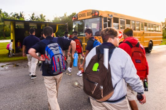 Students board a bus on Ysengsong Road in Dededo to transport them to Astumbo Middle School for the first day of classes on Tuesday, Aug. 14, 2018.