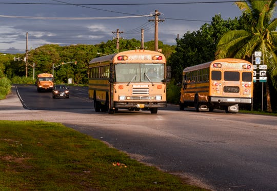 Department of Public Works school buses are seen near the intersection of Ysengsong Road and Route 3 in Dededo, during the morning hustle to transport public school students to their first day of classes on Tuesday, Aug. 14, 2018.