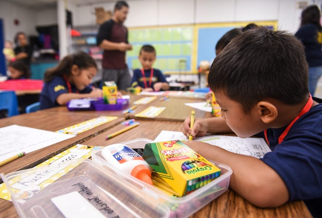 Austin Ceraos, right, and other kindergarten students participated in a coloring activity during their first day of class at Agana Heights Elementary School on Tuesday, Aug. 14, 2018.