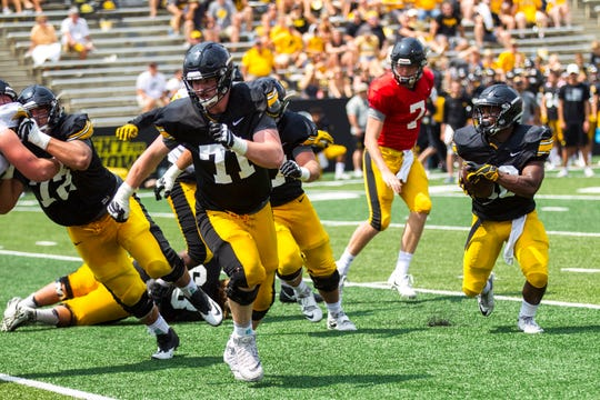 Iowa offensive lineman Mark Kallenberger (71) sets up a block for running back Mekhi Sargent (10) during a Kids Day practice on Saturday, Aug. 11, 2018, at Kinnick Stadium in Iowa City.