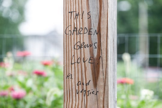 """This Garden Grows Love, P.S., and Veggies"" is scrawled on a post in the Fletcher Place Community Center's 'Seeds of Hope Community Garden Project' at Fletcher Place Community Center in Indianapolis on Friday, Aug. 10, 2018. The garden features a wide variety of fruits and veggies tended to by volunteers."