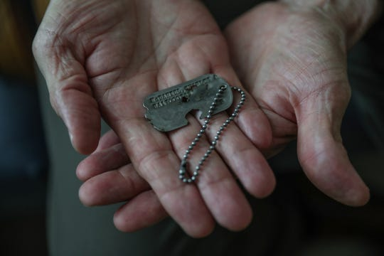 Charles McDaniel Jr., of Indianapolis, shows his father's military dog tag at the Indiana War Memorial on Monday, Aug. 13, 2018. The dog tag was the only identification tag included in the 55 boxes of remains recently returned from North Korea to the U.S.