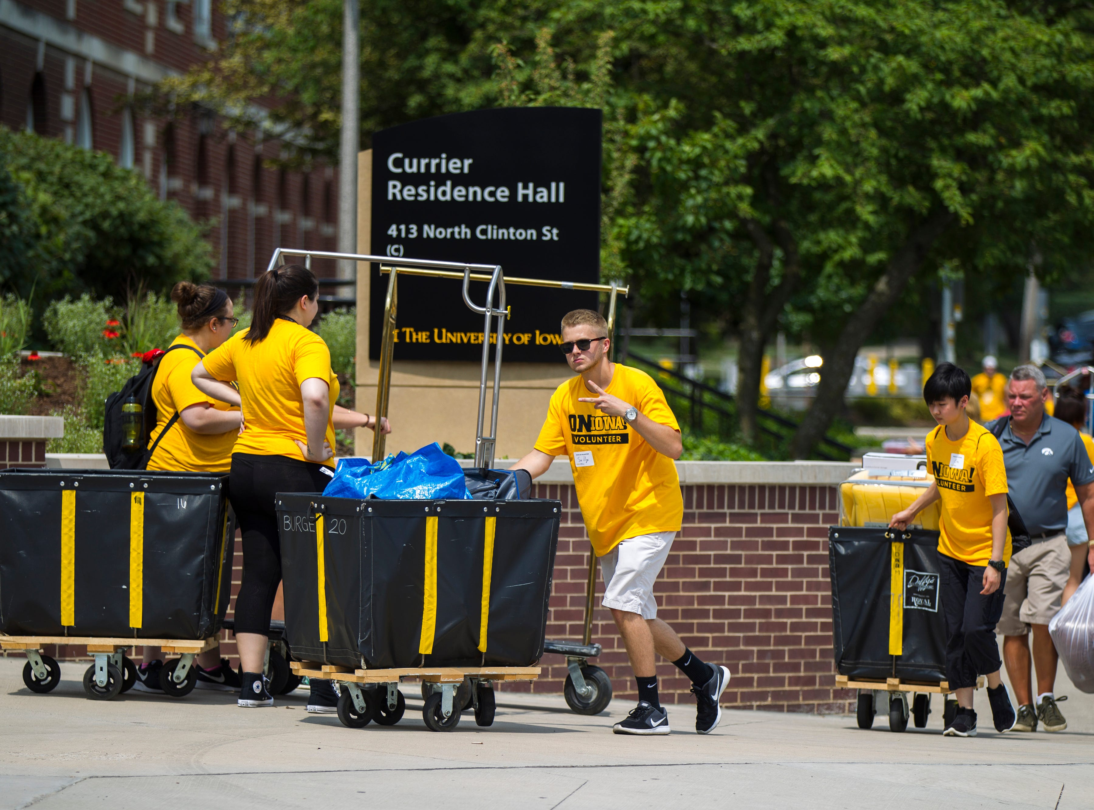 Sully Lown, of Downers Grove, Illinois, helps families along Clinton Street during new student move-in on Tuesday, Aug. 14, 2018, on the University of Iowa campus in Iowa City. Lown is a sophomore preparing for dental school.