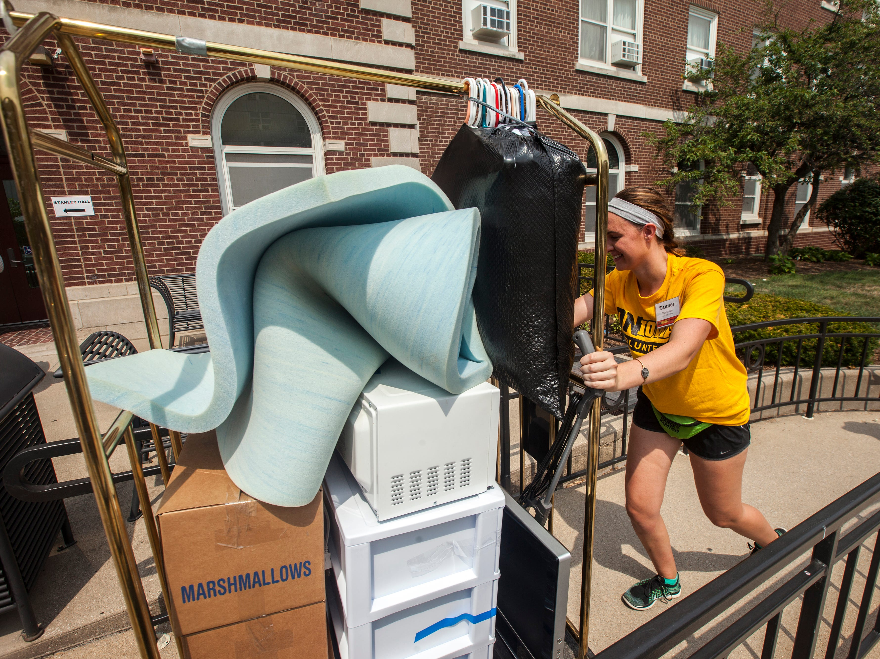 Tanner Thompson, of Bettendorf, Iowa pushes a cart into Currier Residence Hall during new student move-in on Tuesday, Aug. 14, 2018, on the University of Iowa campus in Iowa City. Thompson is a sophomore studying nursing and Spanish.