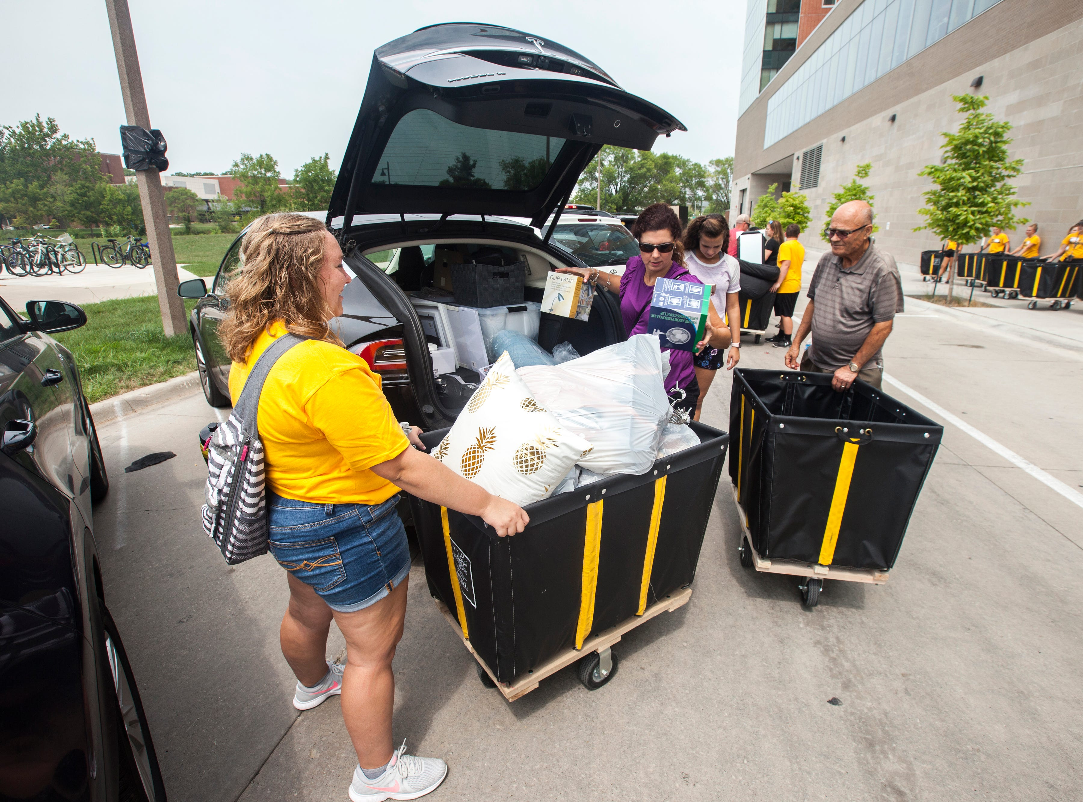 Lindsay Hippen, of Washington, Iowa helps a family at Catlett Residence Hall during new student move-in on Tuesday, Aug. 14, 2018, on the University of Iowa campus in Iowa City. Hippen is a sophomore studying english and creative writing and is a first year OnIowa leader.