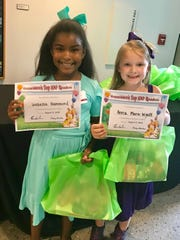 Isabella Hammond (left) and Anna Marie Wyatt show their certificates for taking the Summer Reading Challenge.