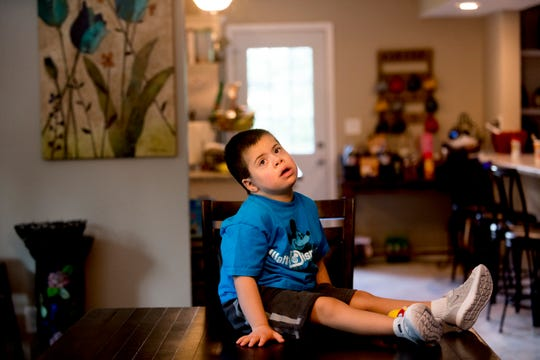 Cobi Carmichael, 6, sits on the table at his home in East Knoxville on Saturday, August 11, 2018. The Carmichaels, who have adopted four children with Down syndrome, received a ramp free of charge built by Amramp of East Tennessee.
