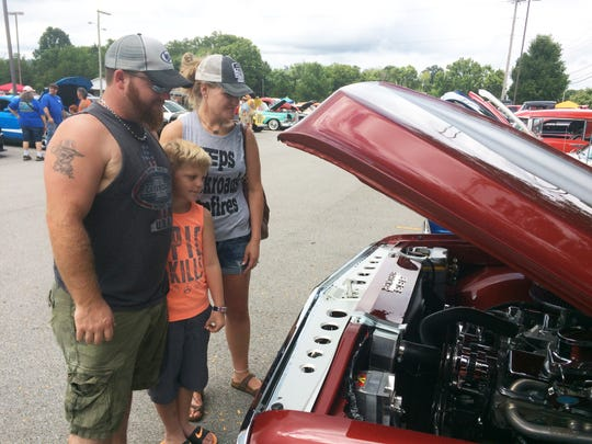 Frank Crane, who grew up with Travis Wegener, spends time at the car show with his wife, Carrie, and son Mason.