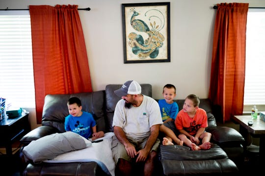 From left, Cobi, dad Sean, foster son Landon and Caden Carmichael hang out in the living room in their home in East Knoxville on Saturday, August 11, 2018. The Carmichaels, who have adopted four children with Down syndrome, received a ramp free of charge built by Amramp of East Tennessee.