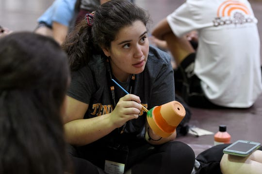 Incoming UTK freshman Gabriela Serrano along with 250 other freshmen and student leaders paint flowerpots to be given to senior living residents and filled backpacks for students Tuesday, August 14, 2018. The team building exercise was for the freshman class which is slated to be the biggest freshman class in the university's history.