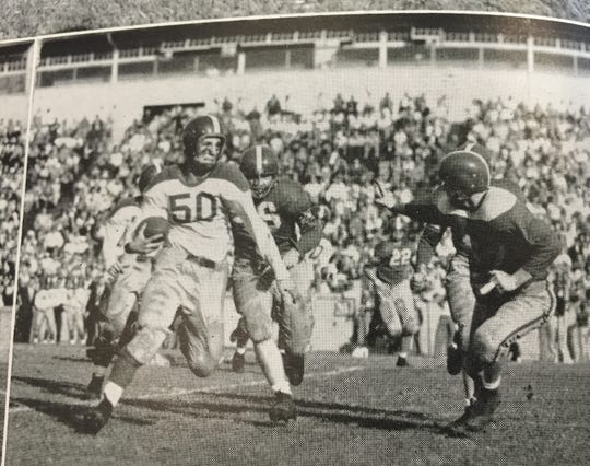 Lafayette Jeff quarterback Bill Bone (50) looks for yardage against West Lafayette during the 1949 game won by the Bronchos 2-0.