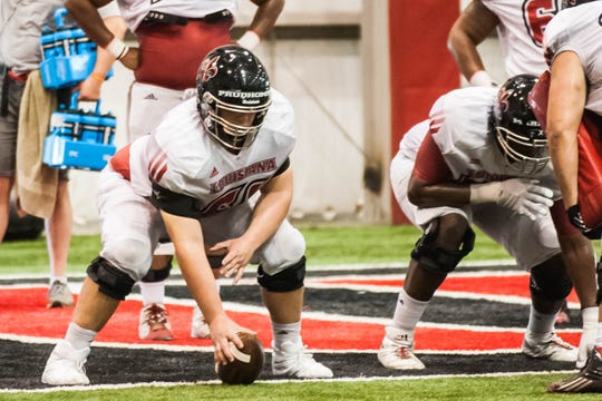 UL center Cole Prudhomme prepares to snap during a practice last August.