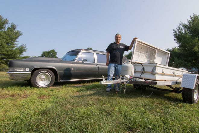 """Tyrone Township resident Frank Hedeen stands next to his """"casketeria"""" mobile grill made of a coffin and his 1969 Cadillac/S. & S. coach hearse Tuesday, Aug. 14, 2018. Hedeen is the founder of the Just Hearse'n Around Club which he expected to have a large presence, including his """"casketeria,"""" at Hell's Hearsefest Sept. 15. The event has officially been cancelled for lack of a permit."""