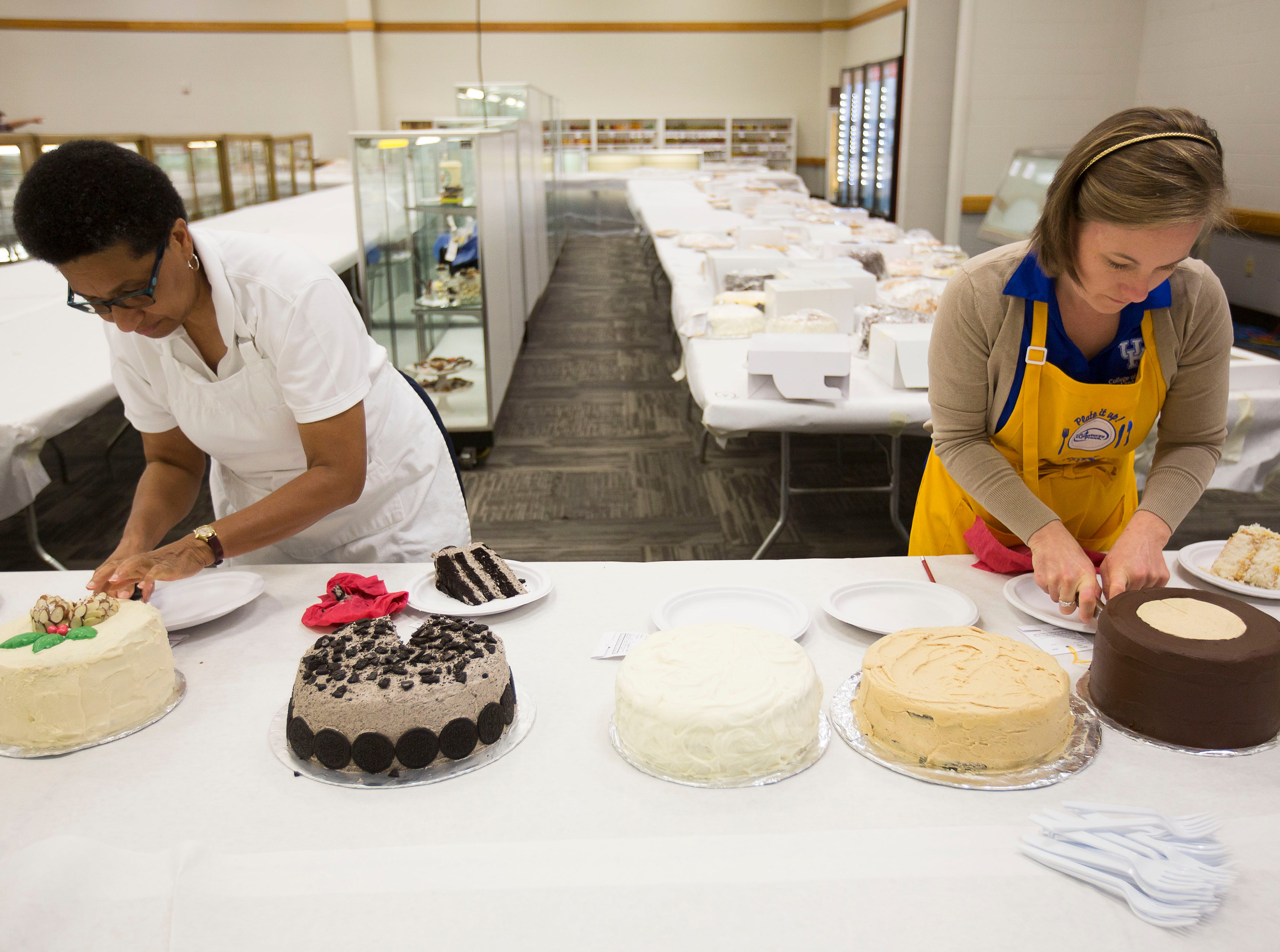 """Valerie Holland, left, and Elizabeth Coots, right, slice cakes to be judged during the """"Favorite Cake"""" taste testing at the Kentucky State Fair on Tuesday, August 14, 2018."""