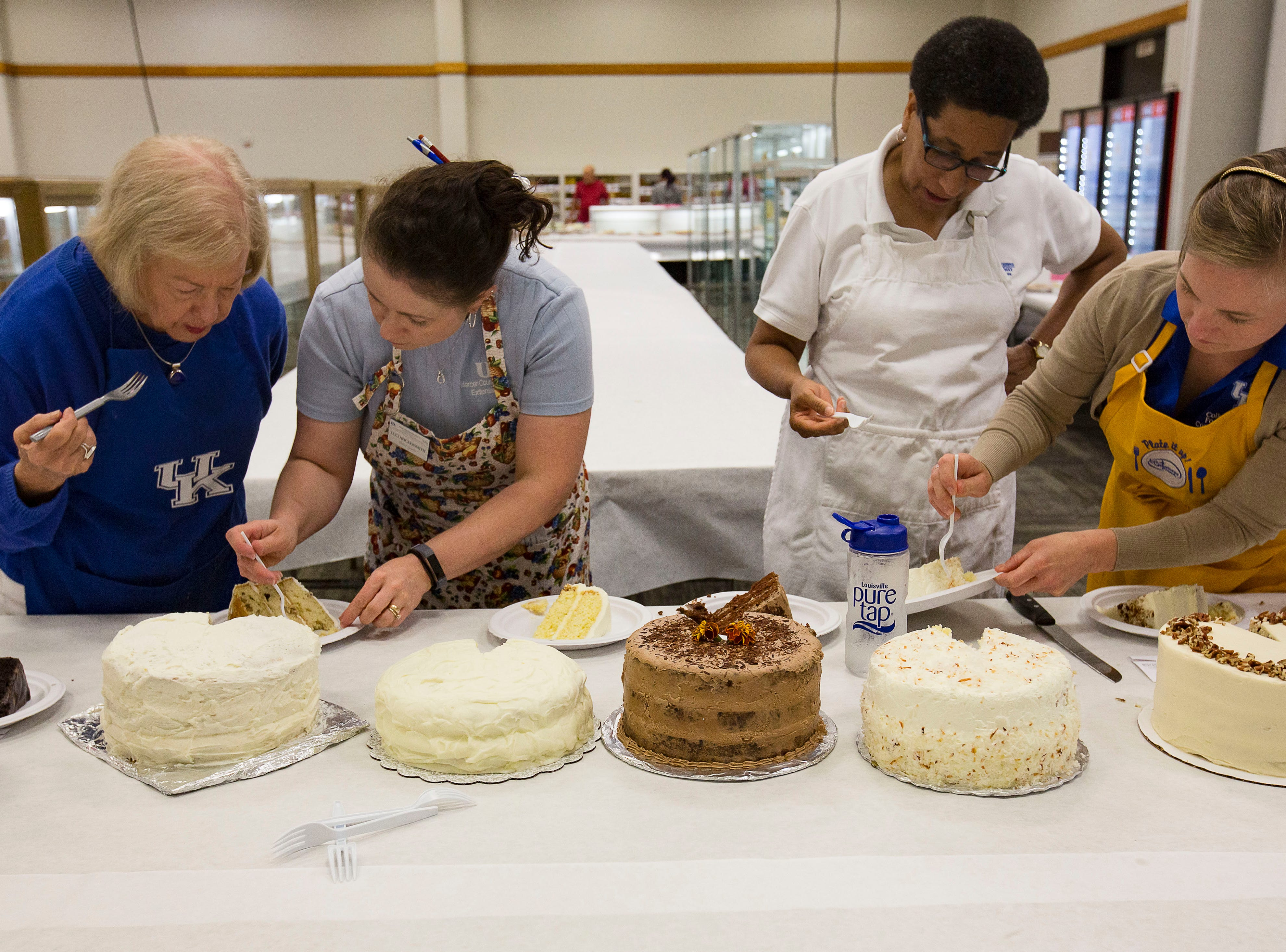 """Left to right, Jeanette Capman, Luci Hocerksmith, Valerie Holland, nd Elizabeth Coots, taste cakes in the """"Favorite Cake"""" category at the Kentucky State Fair on Tuesday, August 14, 2018."""