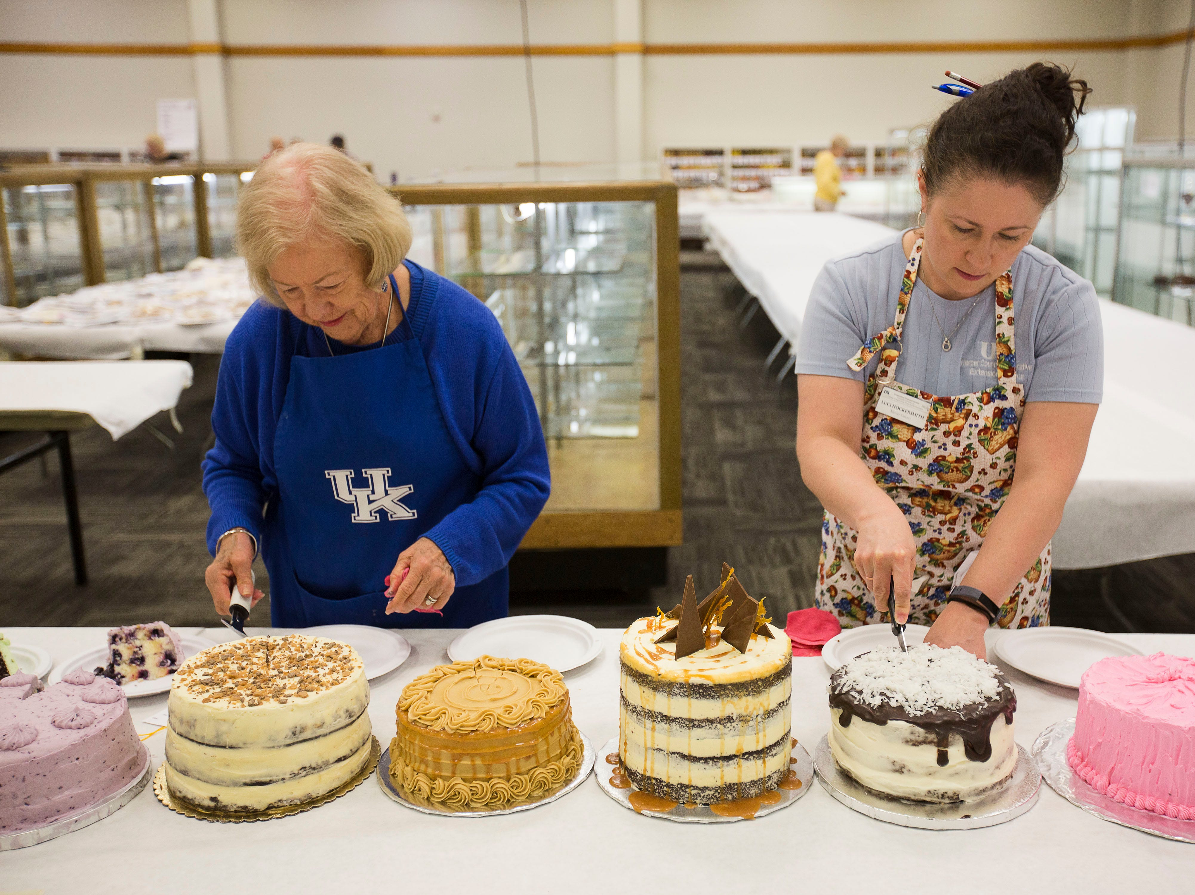 """Jeanette Chapman, left, and Luci Hocerksmith, right, slice slivers of cake to be judged during the """"Favorite Cake"""" taste testing at the Kentucky State Fair on Tuesday, August 14, 2018."""