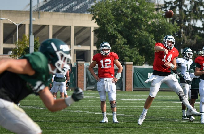 MSU starting QB Brian Lewerke throws during an August practice as backup Rocky Lombardi (12) looks on.