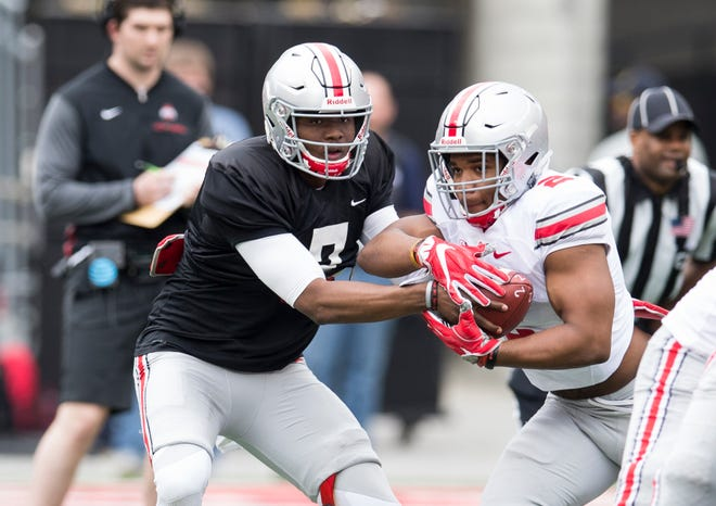 Ohio State's new starting quarterback Dwayne Haskins hands the ball to tailback J.K. Dobbins during the Buckeyes' spring game last April.