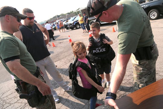 Ontario Police officer Rod Roose (left) and Mansfield Patrolman Paul Webb help Kassie, 6; and JJ Osbun, 8 put on vests during the Richland County Law Enforcement Appreciation Day at O' Charley's Restaurant In Ontario on Tuesday.