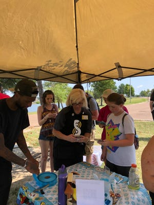 """Kerry Hanan, center, Silph Road master guide for the West Tennessee/North Mississippi area, helps a """"Pokemon Go"""" trainer during a recent meetup at Olive Branch City Park."""