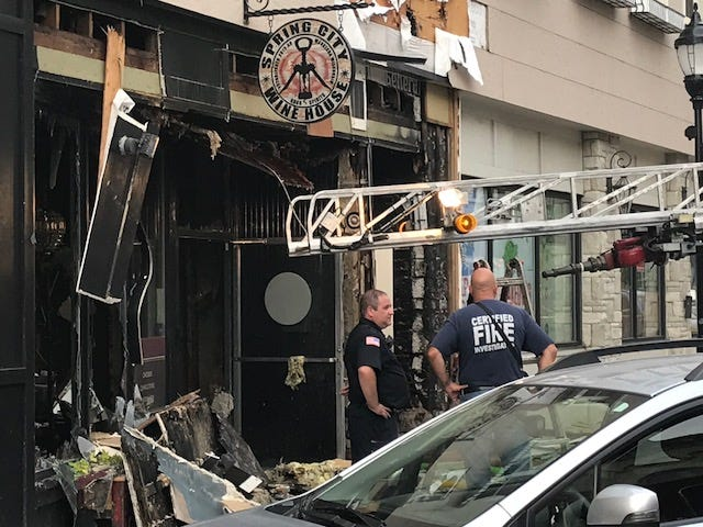 A Waukesha firefighter and police officer discuss an Aug. 14 fire that damaged The Clarke Hotel, Spring City Wine House and The Steaming Cup.