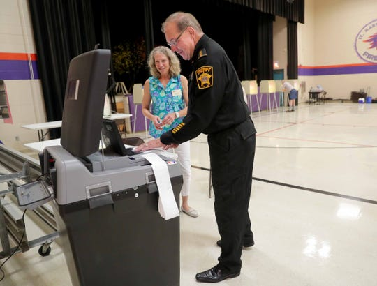 Acting Milwaukee County Sheriff Richard Schmidt feeds his ballot into a scanner as poll worker Monika Sobic looks on at St. Martin of Tours Church on South 116th Street in Franklin on Tuesday.